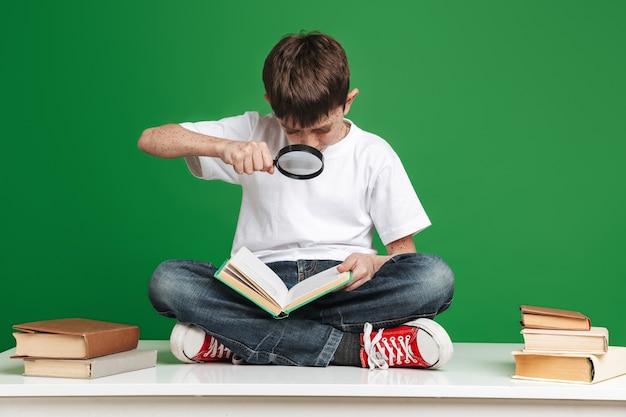 Skoncentrowany młody chłopak czyta książkę z lupą siedząc na stole nad zieloną ścianą