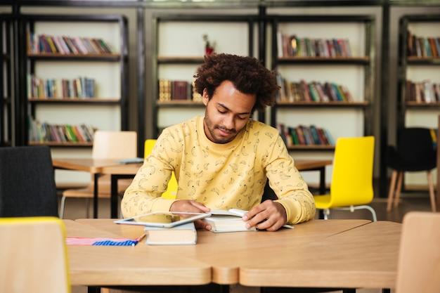 Skoncentrowany młody człowiek czytając książkę i ucząc się w bibliotece