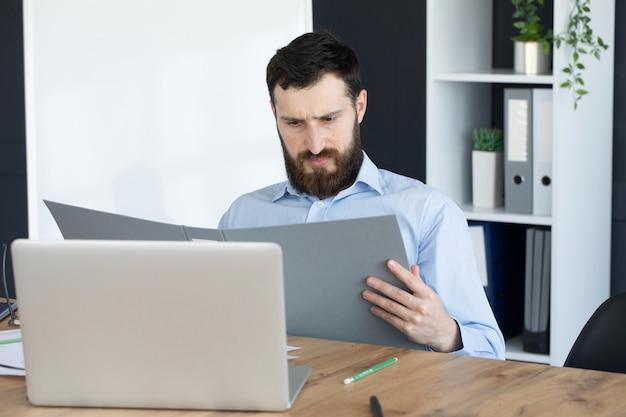 Skoncentrowany młody człowiek pracuje na laptopie w domowym biurze