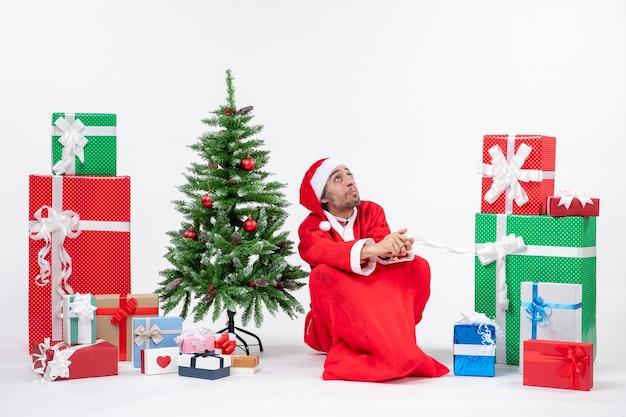 Skoncentrowany młody człowiek przebrany za świętego mikołaja z prezentami i ozdobioną choinką siedzi na ziemi na białym tle
