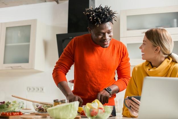 Skoncentrowany młody człowiek przyglądający się uważnie ekranowi laptopa podczas krojenia warzyw, a jego uśmiechnięta dziewczyna patrzy na niego