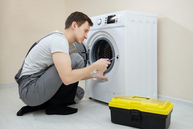 Skoncentrowany młody człowiek przysiada naprawiający zepsutą nowoczesną pralkę za pomocą śrubokręta na drewnianej podłodze przy beżowej ścianie