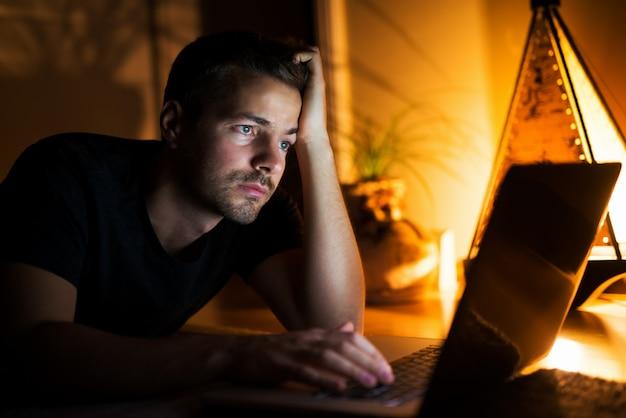 Skoncentrowany młody człowiek szuka informacji w internecie, wygląda na zmęczonego