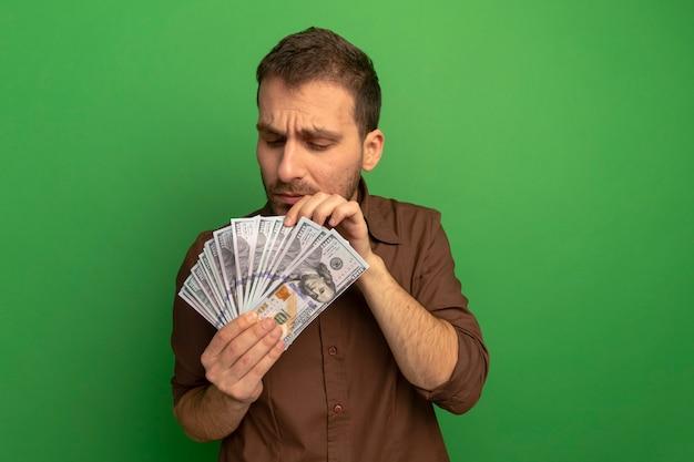 Skoncentrowany młody człowiek trzyma i patrząc na pieniądze, licząc je na białym tle na zielonej ścianie
