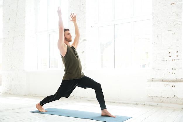 Skoncentrowany młody człowiek uświęcający jogę stanowią na macie fitness
