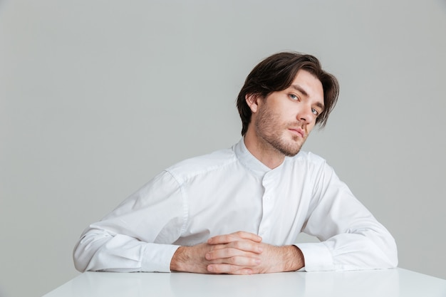 Skoncentrowany młody człowiek w białej koszuli siedzący przy stole ze skrzyżowanymi palcami na białym tle na szarej ścianie