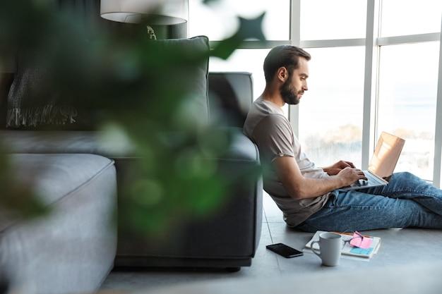 Skoncentrowany młody człowiek w pomieszczeniu w domu za pomocą laptopa siedzieć na podłodze.