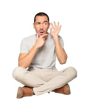 Skoncentrowany młody człowiek wykonujący gest próbujący coś usłyszeć