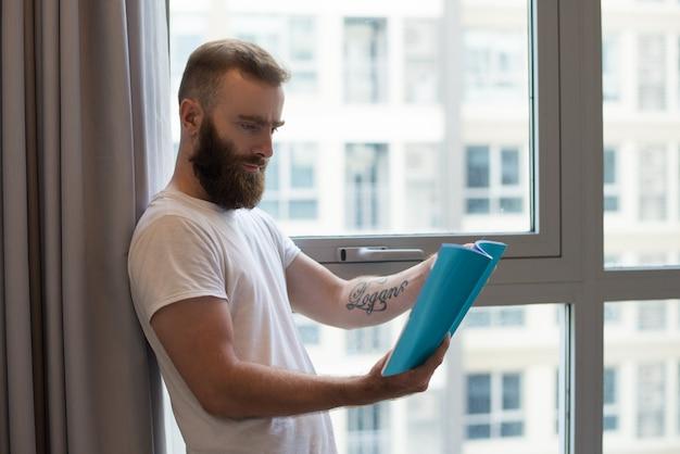 Skoncentrowany młody człowiek z tatuaż czytelniczą książką