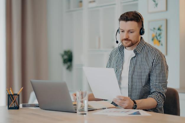Skoncentrowany młody facet siedzi w salonie z zestawem słuchawkowym i za pomocą laptopa, trzymając dokument i patrząc na niego, mężczyzna freelancer analizujący dane biznesowe. praca zdalna w domu