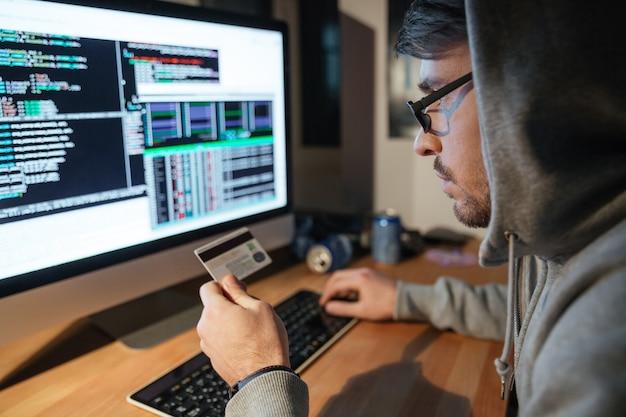 Skoncentrowany młody haker w okularach kradnący pieniądze z różnych kart kredytowych siedzący w ciemnym pokoju