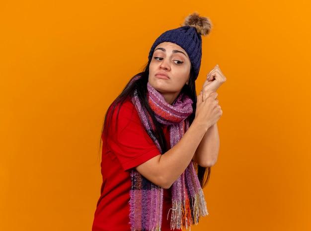 Skoncentrowany młody kaukaski chora dziewczyna ubrana w czapkę zimową i szalik sprawdzający puls patrząc z boku na białym tle na pomarańczowej ścianie z miejsca na kopię