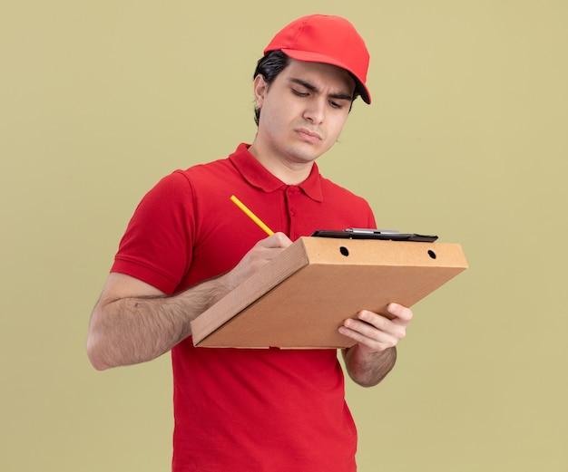 Skoncentrowany młody kaukaski dostawca w niebieskim mundurze i czapce, trzymający paczkę pizzy i schowek na nim, piszący ołówkiem w schowku