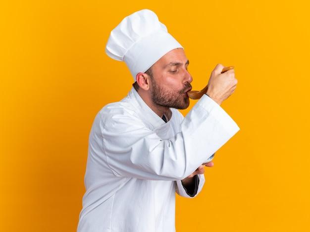 Skoncentrowany młody kucharz kaukaski w mundurze szefa kuchni i czapce stojącej w widoku profilu trzymając miskę testową z łyżką odizolowaną na pomarańczowej ścianie
