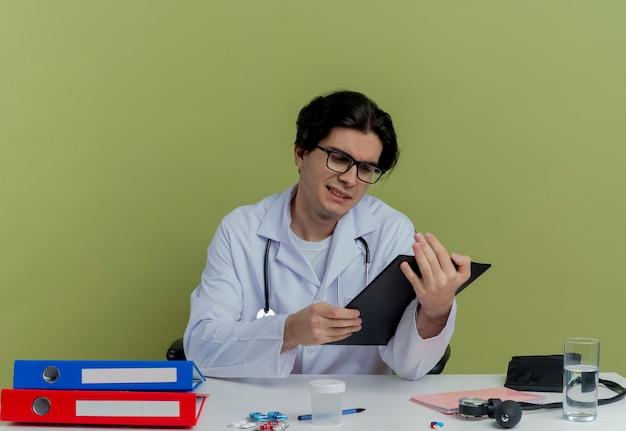 Skoncentrowany młody lekarz płci męskiej ubrany w szlafrok medyczny i stetoskop w okularach siedzi przy biurku z narzędziami medycznymi, trzymając i patrząc na schowek na białym tle