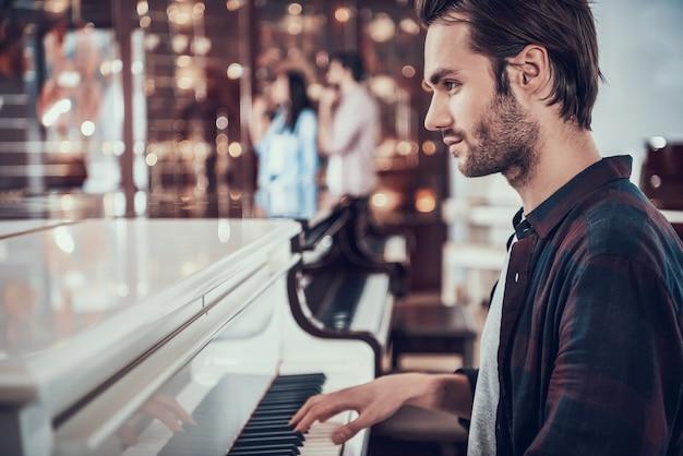 Skoncentrowany młody mężczyzna gra na fortepianie