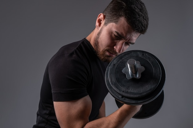 Skoncentrowany młody mężczyzna robi loki na biceps z hantlami