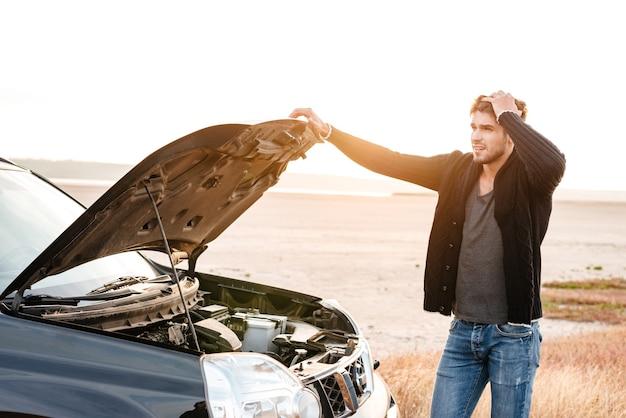 Skoncentrowany młody mężczyzna trzymający się za ręce na masce pojazdu i zaglądający do środka, stojąc na zewnątrz