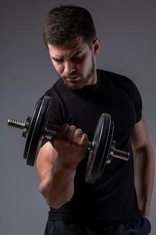 Skoncentrowany młody mężczyzna wykonujący uginanie bicepsa z hantlami