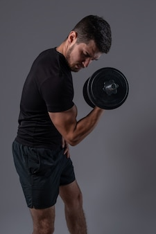 Skoncentrowany młody mężczyzna wykonujący uginanie hantle na biceps