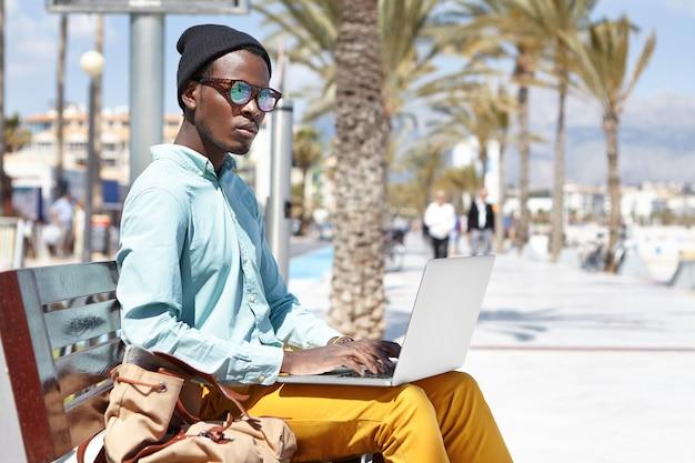 Skoncentrowany młody niezależny pracownik korzystający z komputera przenośnego do pracy zdalnej