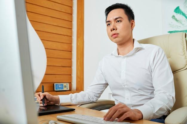Skoncentrowany młody projektant korzystający ze stołu graficznego podczas pracy nad logotypem nowego produktu