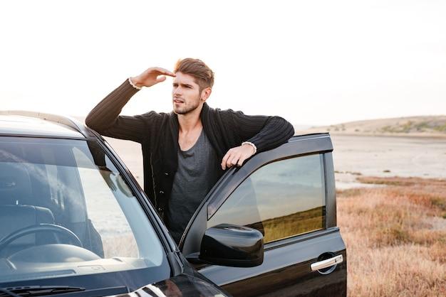 Skoncentrowany młody przypadkowy mężczyzna stojący przy swoim samochodzie zaparkowanym nad morzem