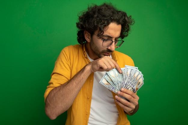 Skoncentrowany młody przystojny kaukaski mężczyzna w okularach liczenie pieniędzy na białym tle na zielonej ścianie z miejsca na kopię