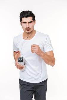 Skoncentrowany młody sportowiec biegający ze słuchawkami i butelką na wodę na białym tle