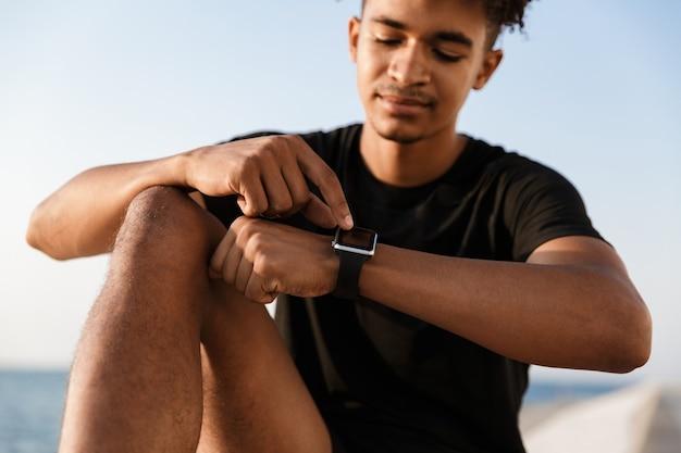 Skoncentrowany młody sportowiec siedzi na świeżym powietrzu na plaży za pomocą zegarka