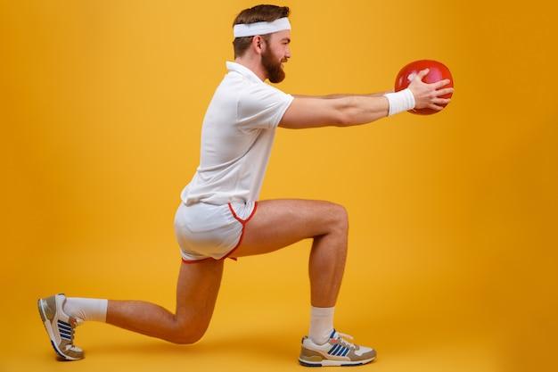 Skoncentrowany młody sportowiec wykonuje ćwiczenia sportowe trzymając piłkę.