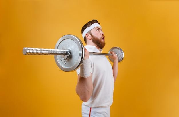 Skoncentrowany młody sportowiec wykonuje ćwiczenia sportowe ze sztangą
