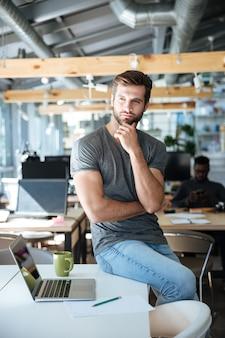 Skoncentrowany myślący młodego człowieka obsiadanie na stole w biurze