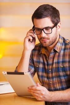 Skoncentrowany na pracy. przekonany, młody człowiek rozmawia przez telefon komórkowy i patrząc na cyfrowy tablet siedząc w kawiarni