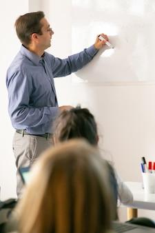 Skoncentrowany nauczyciel rysujący na tablicy i wyjaśniający lekcję uczniom