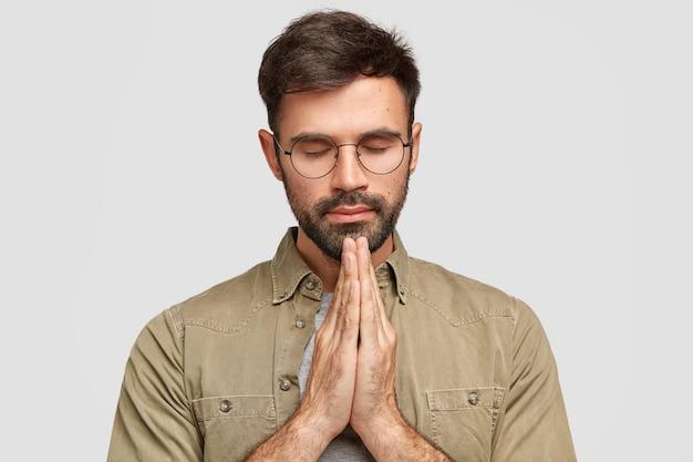 Skoncentrowany, nieogolony mężczyzna stoi w geście modlitwy, ściskając dłonie