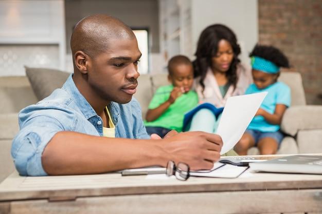 Skoncentrowany ojciec czytający papier