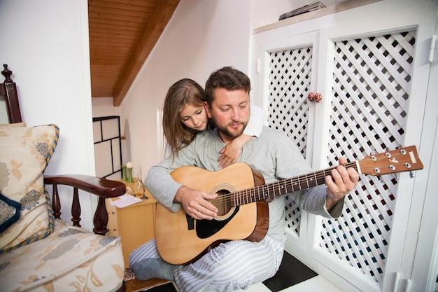 Skoncentrowany ojciec gra na gitarze z córką patrząc na niego