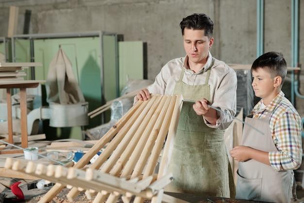 Skoncentrowany ojciec w fartuchu, wkładający metalowy patyk w otwory w drewnianych deskach podczas montażu krzesła z synem w warsztacie stolarskim