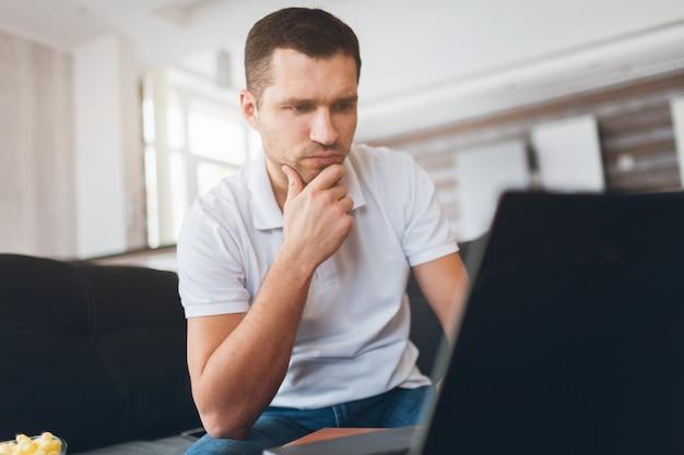 Skoncentrowany, pewny siebie facet oglądający mecz sportowy, grę lub program. oglądaj także film lub film. intensywność patrzenia na ekran.