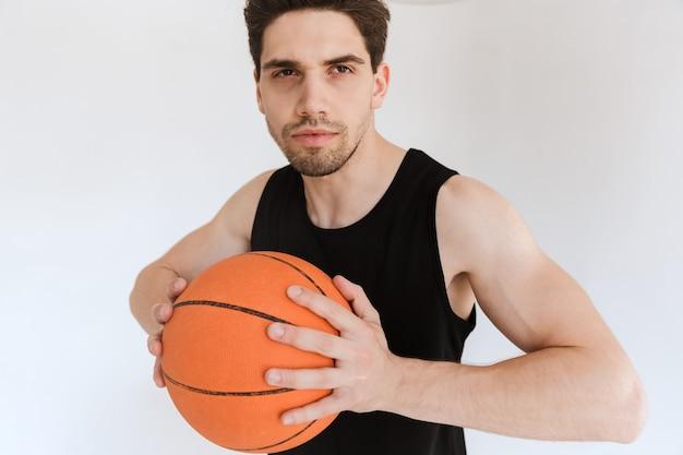 Skoncentrowany poważny silny młody sportowiec koszykarz trzymając piłkę na białym tle.