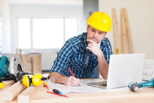 Skoncentrowany pracownik budowlany na budowie