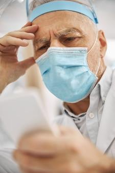 Skoncentrowany pracownik służby zdrowia marszczy brwi i patrzy na swojego smartfona