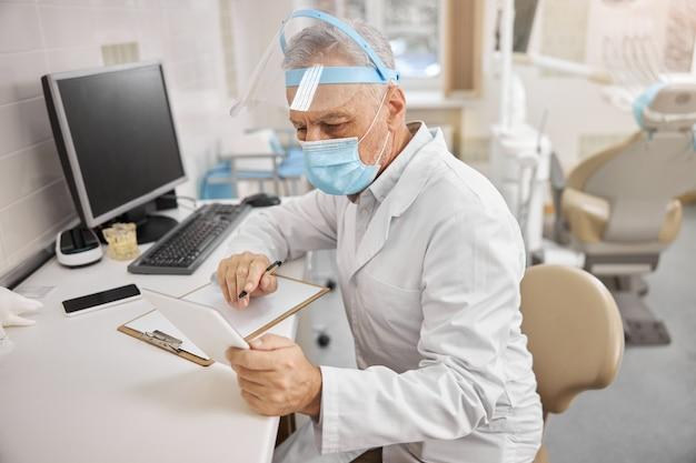 Skoncentrowany pracownik służby zdrowia w masce i fartuchu laboratoryjnym patrzący na tablet siedząc przy biurku