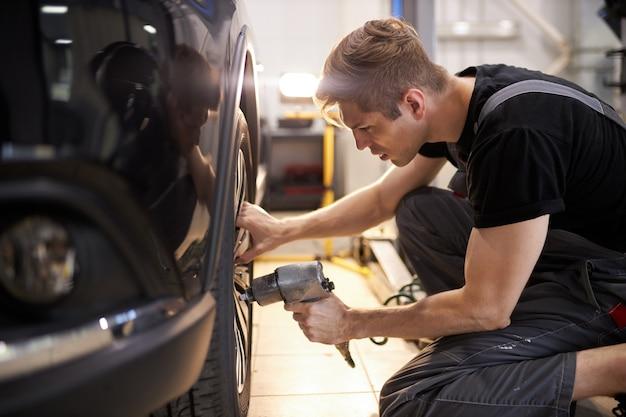 Skoncentrowany profesjonalny mechanik samochodowy naprawia pęknięte koło