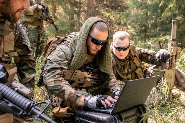 Skoncentrowany programista wojskowy w okularach przeciwsłonecznych korzystający z komputera wojskowego podczas nawiązywania kontaktu z bazą wojskową w lesie