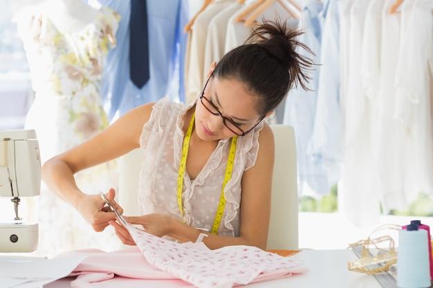 Skoncentrowany projektant mody pracujący na tkaninach