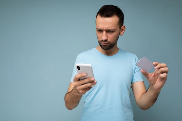 Skoncentrowany przystojny mężczyzna ubrany w codzienne ubrania na białym tle na ścianie, trzymając i używając telefonu i karty kredytowej dokonywania płatności, patrząc na ekran smartfona.