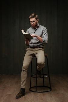 Skoncentrowany przystojny młody brodaty mężczyzna w okularach siedzący i czytający książkę odizolowaną na czarnej drewnianej powierzchni