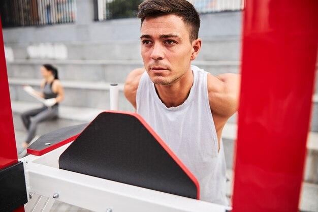 Skoncentrowany, silny młody mężczyzna robi podciąganie tricepsa na maszynie na świeżym powietrzu w mieście